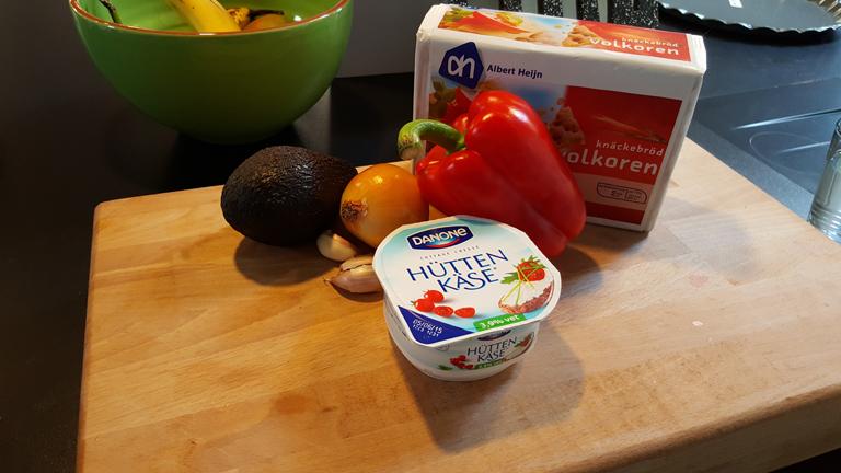 De ingrediënten voor de guacamole; avocado, ui, paprika, hüttenkäse, knoflook en volkoren knäckerbröd