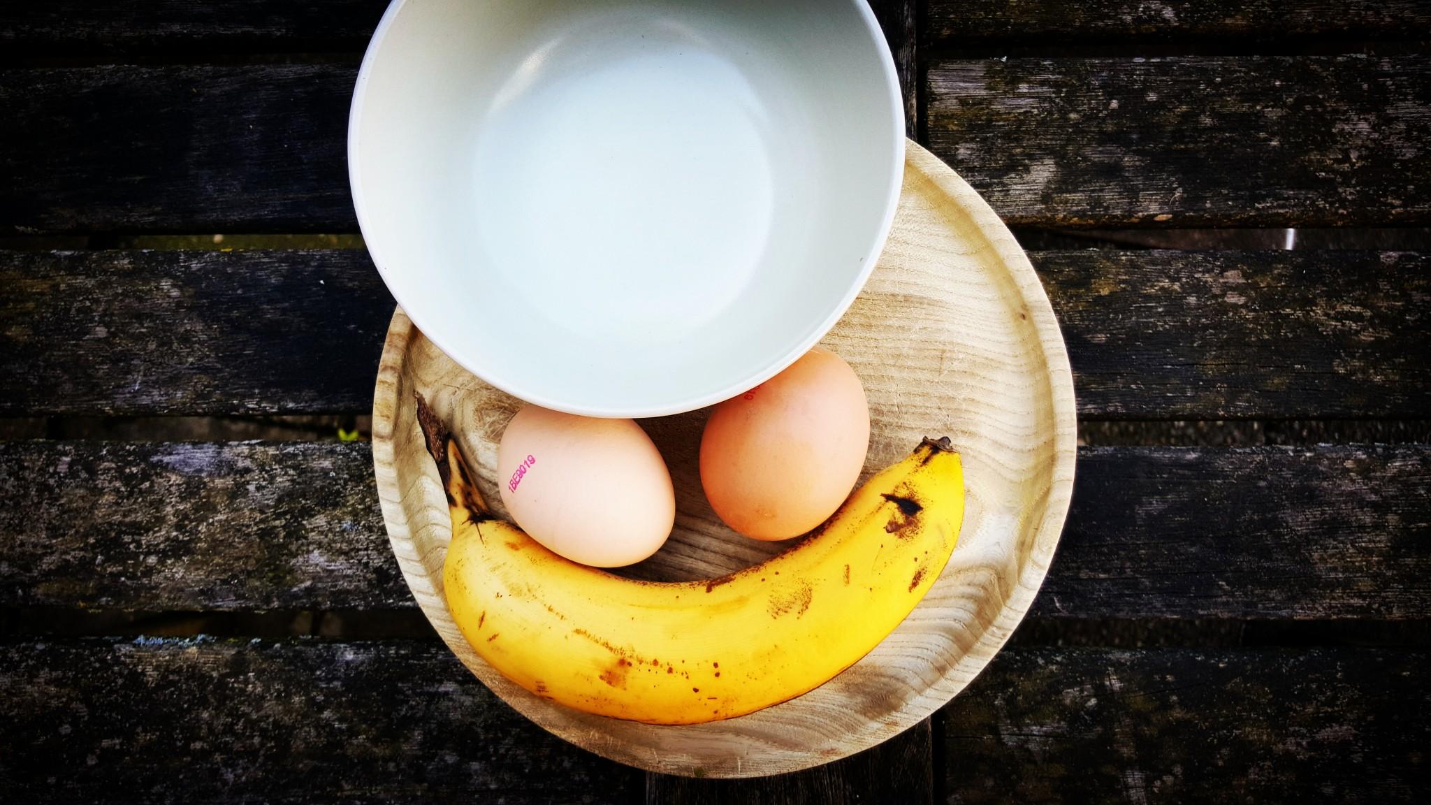 Ingrediënten en benodigdheden voor een bananenpannenkoek, twee eieren, een rijpe banaan en een kommetje.